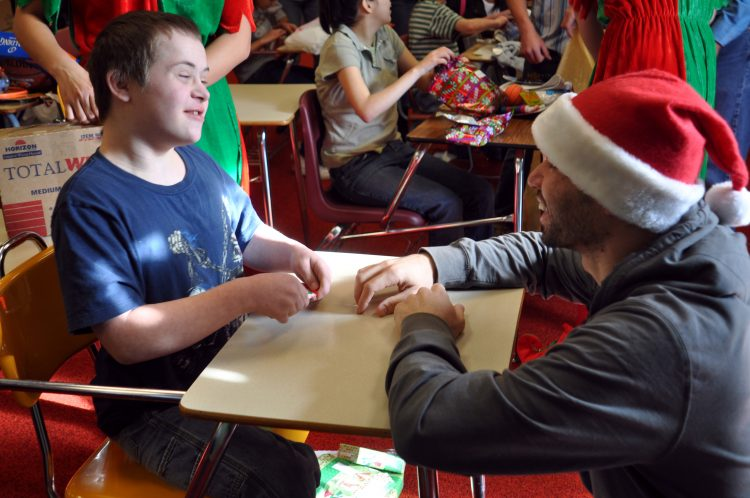 teacher wearing a Santa Claus hat working with a young student